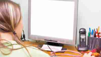 A blank computer screen, girl staring at it