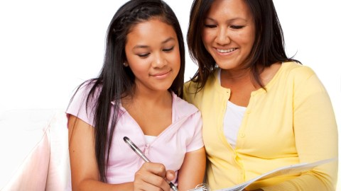 A mother works on homework with her daughter. Quality time is one way to motivate a teenager.