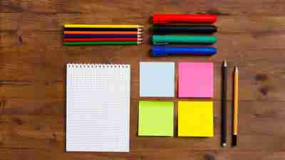 Set of colorful office supplies on old wooden table. Organization hack: bright objects are harder to lose.