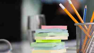 A pile of sticky notes sits on a desk, ready to mark where to pick back up again when you need to step away from a task.