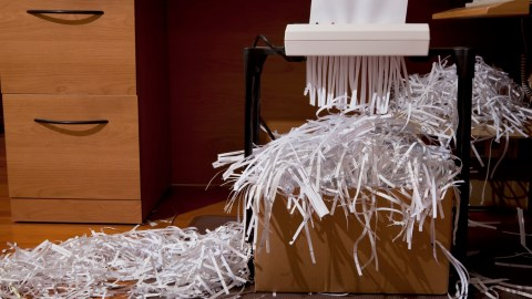 A paper shredder overflowing with paper in the disorganized office of a person with ADHD.