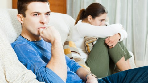 A man and woman both look upset on the couch, after an argument about how to stop negative thoughts