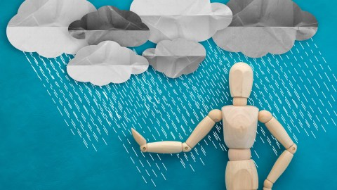 Rain falling on a wooden figure, a metaphor for when negative thoughts cloud your day