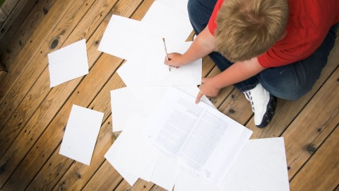 A disorganized child experiencing frustration while surrounded by homework papers