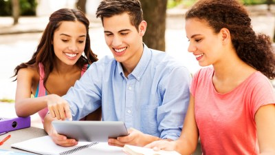 A teen with ADHD uses assistive technology at an outdoor table while two other students look on.