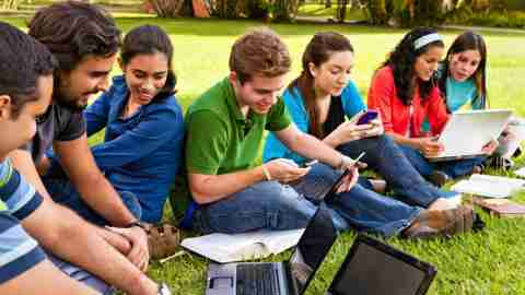 A group of high school students use assistive technology together on a lawn.