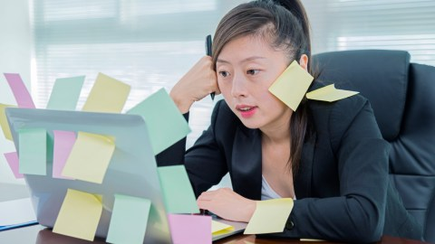 Businesswoman covered in post-it notes and looking stressed without her positive affirmations