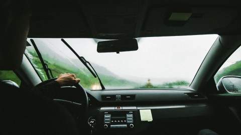 A man driving in the rain — an example of what it feels like to have ADHD.