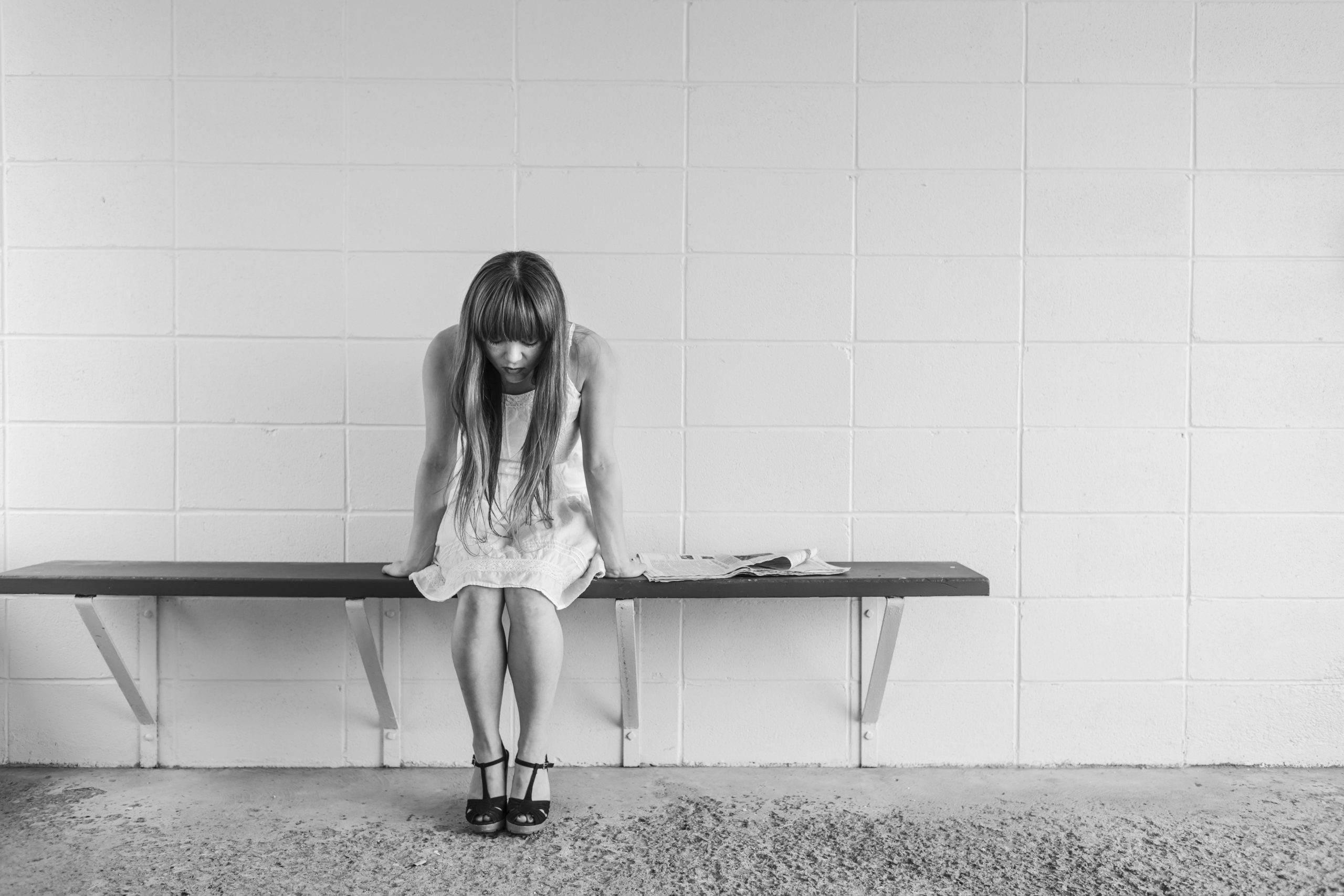 """Woman showing signs of autism in adults sits alone on a bench feeling emotional because she worries """"I think I have ADHD."""""""