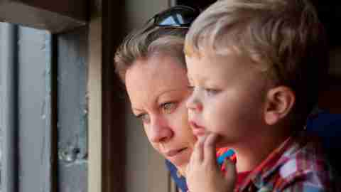 A mother and her child with a language processing disorder look at the window