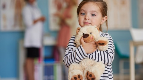 A girl with a language processing disorder hugs a teddy bear