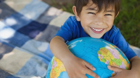 """A smiling boy holds a globe and wonders, """"How does ADHD medication work?"""""""