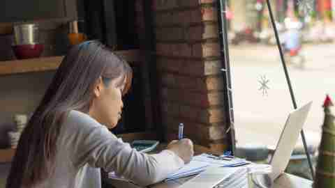 "A young woman works on paperwork at a cafe, and wonders, ""How does ADHD medication work?"""