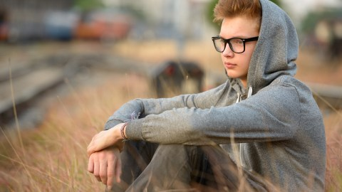 """A boy sits in tall grass with his hood on, and wonders, """"How do ADHD medications work?"""""""