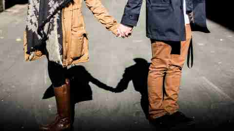 A man and woman hold hands facing away from each other after having an argument about how to be a better dad.