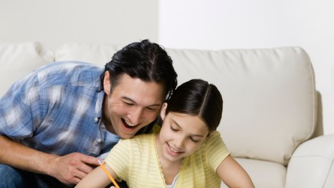 A father works on mending his relationship with his child by helping her with her homework
