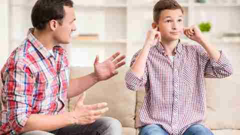 Son covering ears while father scolds him and wonders how he'll mend their relationship
