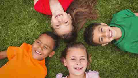 Four kids with ADHD lay on the grass with their heads in a circle looking up at YouTube videos on an overhead screen