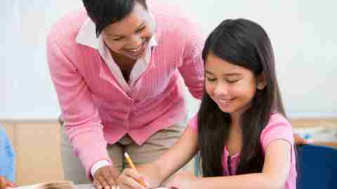 A teacher working with a student to improve her education