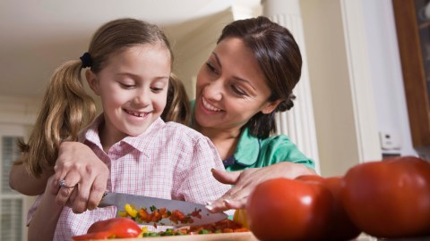 Mother and daughter cooking together as a reward for good behavior