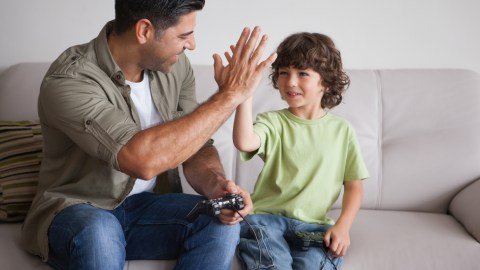Father playing video games with his son who has ADHD, anxiety, and autism