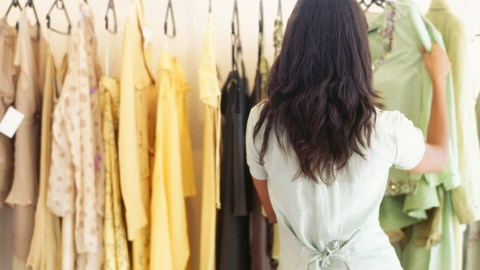 rear view of a woman with SPD choosing a dress in a clothing store