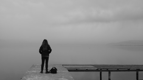 A woman with ADHD stands on a dock and looks into the distance