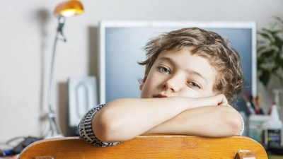 Boy with ADHD folds arms over back of chair in front of work desk looking bored