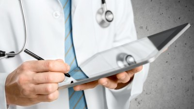 Doctor in white jacket with stethoscope around neck making notes in ipad for ADHD patient