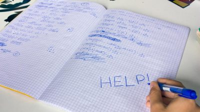Emotional student with ADHD writing HELP in notebook