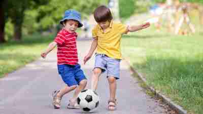 Two young boys with ADHD playing soccer outside in the summer
