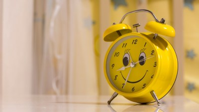 Yellow alarm clock on side table in room belonging to ADHD child to limit their video game playing time. ey spend on video games