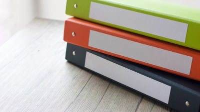 Colorful binders organized well and stacked on wooden table belonging to ADHD student