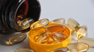 Close-up of omega-3 fish oil capsules spilling out of container, a good source of essential fatty acids for people with ADHD