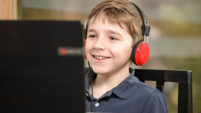 Boy with ADHD wearing headphones, smiling, and working on computer at desk