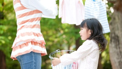 Daughter with ADHD holding laundry basket while mom hangs clothing outside