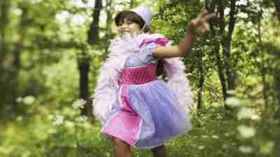 Girl with ADHD dressed up as princess plays game while running outside through woods