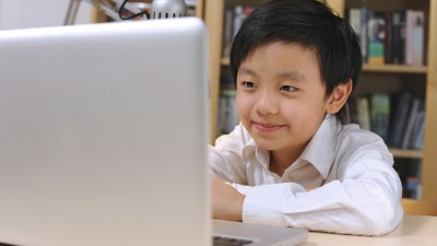 Boy with ADHD in sitting in front of laptop smiling with bookshelf behind him
