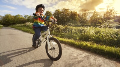 Boy with ADHD riding bike on street outside in forested area