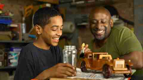A father and son with ADHD work on a wooden car together.