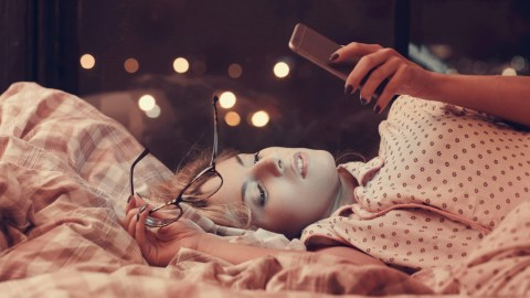 Woman with ADHD is sleepless and stares at her phone in bed.