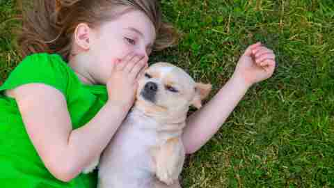 Girl with language processing disorder whispering secrets to a sneaky pup