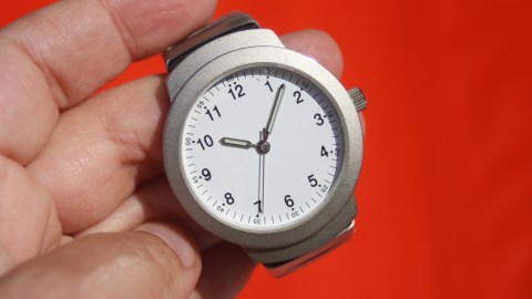 A man holding a watch he'll use for teaching kids time management