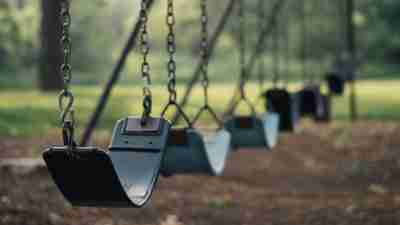 Empty swings. A boy who is feeling different has no one to play with at recess