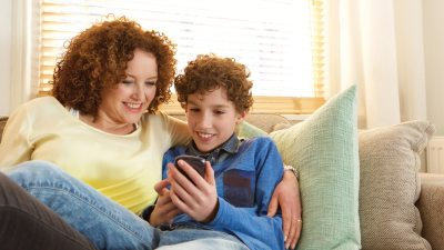 A mother teaching her child how to make friends using a cell phone
