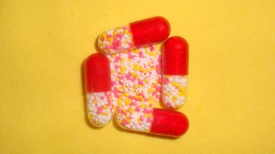 ADHD medication capsules on a bright yellow background