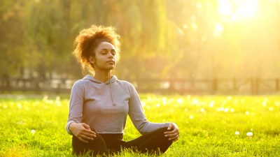 Young ADHD woman meditating in nature