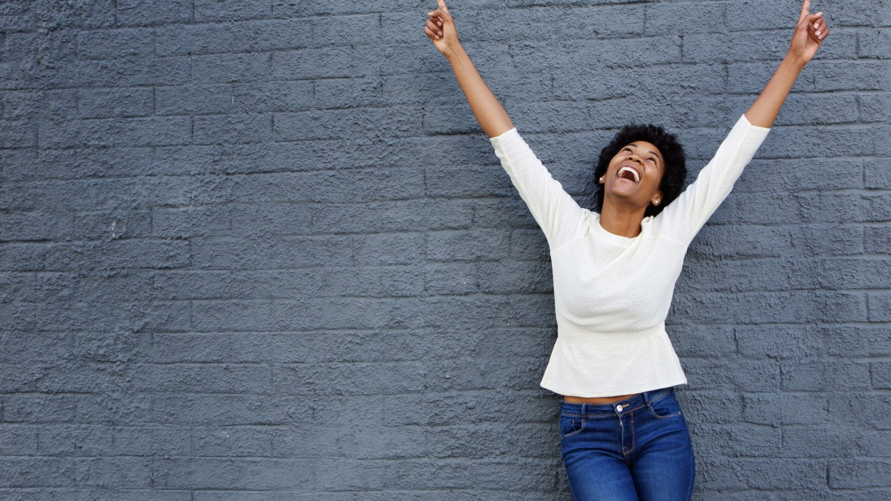 Portrait of a cheerful ADHD woman with hands raised pointing up
