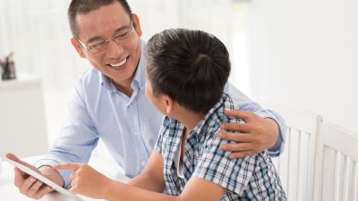 Asian father and ADHD son talking and using digital tablet