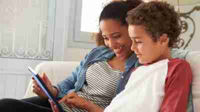 Mother And ADHD Son Sitting On Sofa Using Digital Tablet
